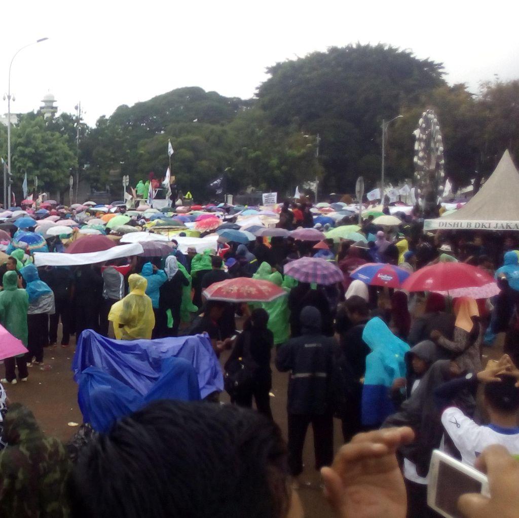 Gerimis, Ribuan Tenaga Honorer Bertahan di Depan Istana dengan Jas Hujan