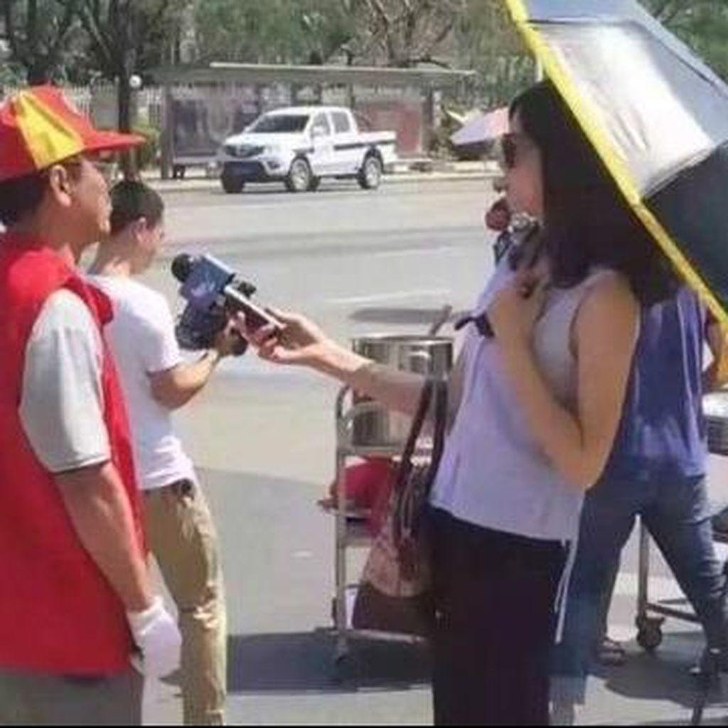Wartawan China Diskors karena Pakai Payung dan Kacamata Hitam Saat Wawancara