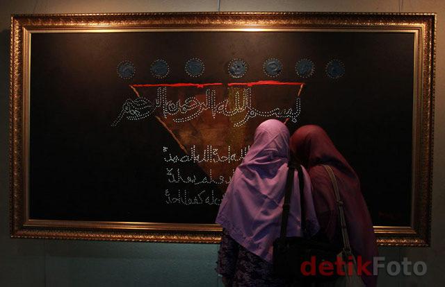 Pengunjung melihat kaligrafi yang dipamerkan.
