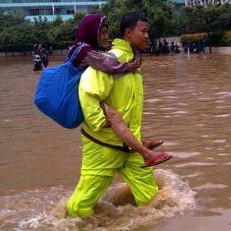 Hebat! Polisi Ini Gendong Nenek Amsinah Lintasi Banjir di Bundaran HI