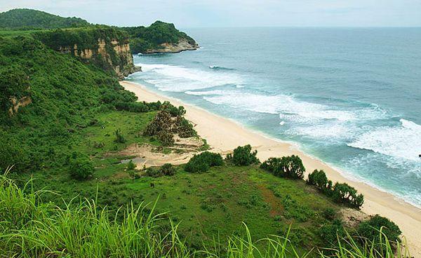 Tampak bukit hijau di depan pantai