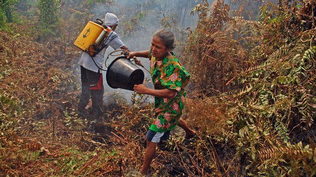Sejumlah warga berusaha memadamkan api yang membakar kebun dengan alat seadanya di Desa Bokor, Kecamatan Rangsang Barat, Kabupaten Kepulauan Meranti, Riau, Selasa (15/3). (ANTARA FOTO/Rony Muharrman)