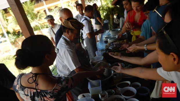 Para pengunjung Manisan, Ubud, berebut lawar, salad khas Bali, yang baru saja dibuat oleh juru masak Darta.