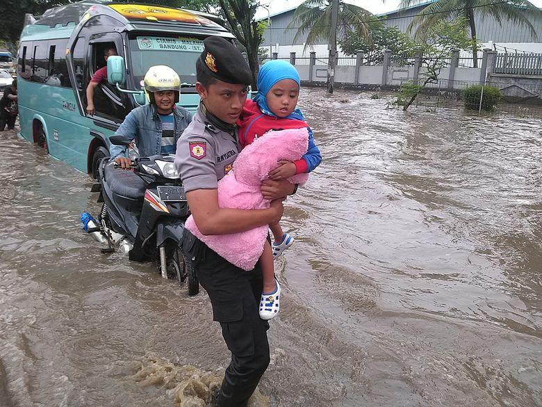 Ketika Polisi Gendong Anak-anak Terobos Genangan Banjir di Jalan Rancaekek