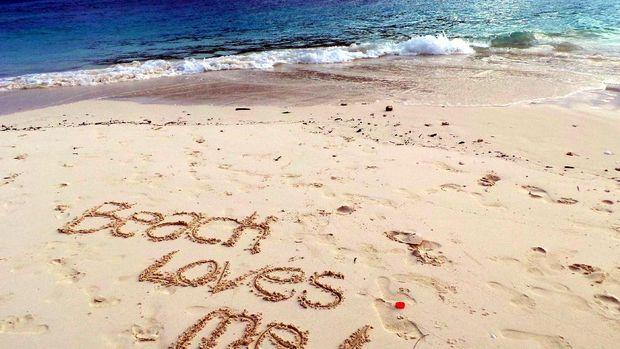 Menuliskan kata-kata di tepi pantai (Wahyu/detikTravel)