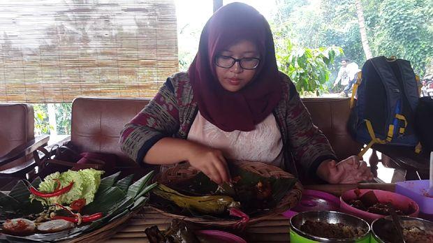 Farah asyik mencoba kuliner nasi lemeng (Putri Akmal/detikTravel)