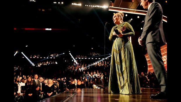 Adele saat menerima penghargaan di atas panggung.