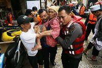 Petugas mengevakuasi warga dari banjir, Selasa (21/2).
