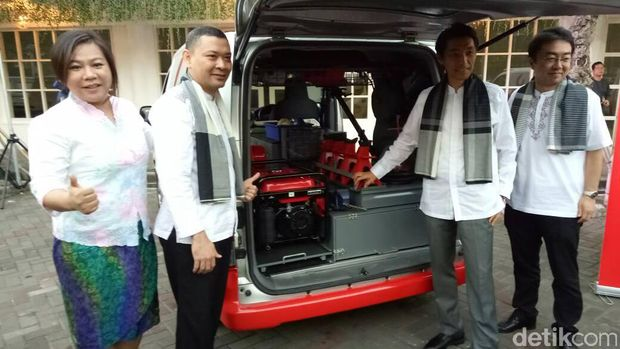 Manajemen Nissan berpose di mobil servis