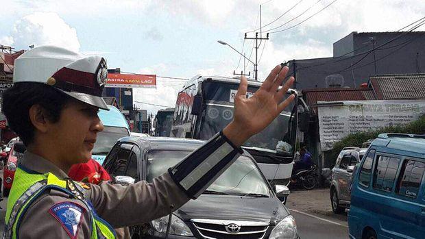 Polisi mengatur arus lalu lintas di jalur Puncak, Senin (26/6/2017)