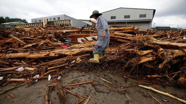 Warga setempat berjalan di antara puing-puing yang terbawa arus banjir