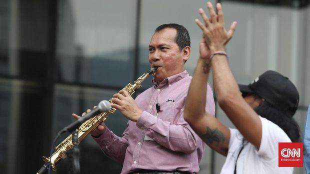 Wakil Ketua KPK Saut Situmorang dengan flute mengiringi Slank, di halaman kantor KPK, Jakarta, Kamis (13/7). Ia menyebut, korupsi akan tetap merajalela jika tak ada dukungan Pemerintah melalui rencana pemberantasan korupsi yang jelas.