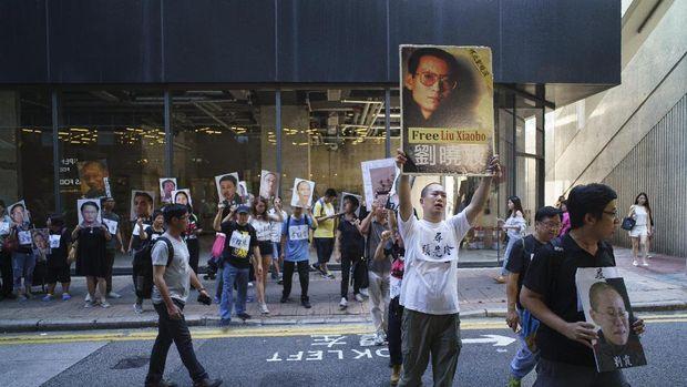 Demonstran pro demokrasi di Hong Kong mengacungkan foto pemenang Nobel Perdamaian Liu Xiaobo dan istrinya Liu Xia dalam sebuah aksi protes di Hong Kong, Juni lalu.