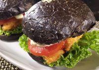 Burger hitam dengan isian fish fingers.