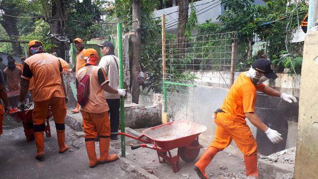 Pasukan Oranye juga ikut membantu membersihkan sisa-sisa reruntuhan bangunan liar.