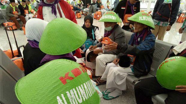 Warna caping jemaah cukup mencolok, hijau terang. Ada tulisan KBIH Al Munawaroh.