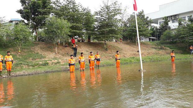 Petugas upacara memakai seragam pasukan oranye dan berpeci