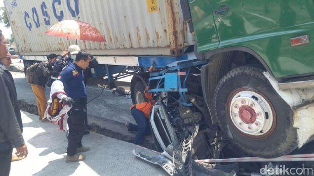 Proses evakuasi korban yang masih terjepit badan mobil.