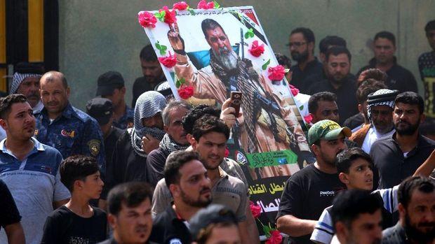Para pelayat Irak menyimpan potret Abu Tahsin al-Salhi saat pemakamannya di dekat kota selatan Basra