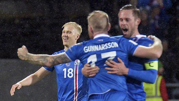 Hordur Magnusson, Aron Gunnarson dan Gylfi Sigurdson (kiri-kanan) rayakan keberhasilan Islandia merebut tiket Piala Dunia untuk kali pertama.