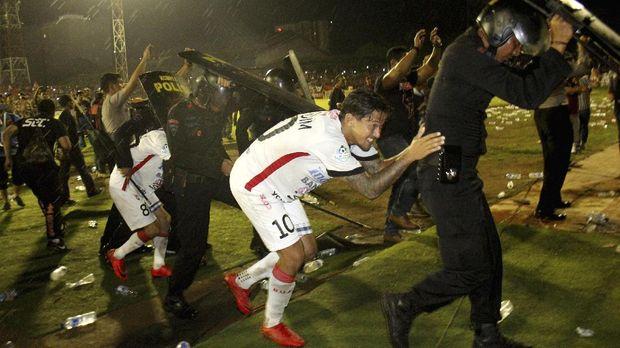 Irfan Bachdim dan kawan-kawan berlindung di balik tameng aparat keamanan saat rusuh di Stadion Andi Mattalatta. (
