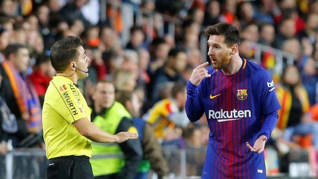 Lionel Messi berbicara dengan hakim garis Enrique Ramos usai insiden kontroversial Barcelona melawan Valencia.
