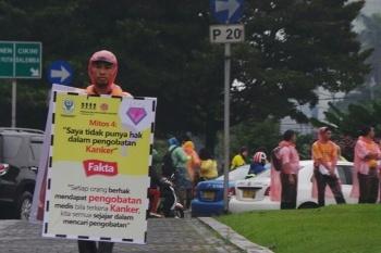 Hujan Tak Halangi Aksi Bagi-bagi Bunga di Hari Kanker Sedunia