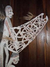 Ukiran patung Asmat memegang sesuatu