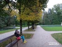 Duduk santai di Istana Hellbrunn dengan guguran daun daun kuning yang eksotis