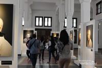 pengunjung diantara lukisan yang dipamerkan