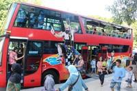 Saat berhenti di depan Bank Indonesia penumpang asyik berfoto bersama bus yang berwarna merah terang ini