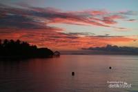 Warna jingga kemerahan mulai menghiasi awan saat matahari memasuki horison.