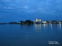 Terlihat Kota Tanjung Balai yang berada di tepi aliran Sungai Asahan. Cahaya lampu-lampu kota di saat senja terlihat menawan saat memantul di aliran sunga berpadu dengan kapal-kapal yang lalu lalang
