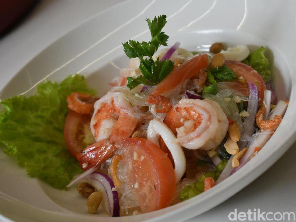 Glass Noodle Salad with Chicken and Shrimps disajikan secara cantik dengan kombinasi warna menarik. Suun yang lembut dipadukan dengan lettuce, potongan cumi dan udang yang empuk.