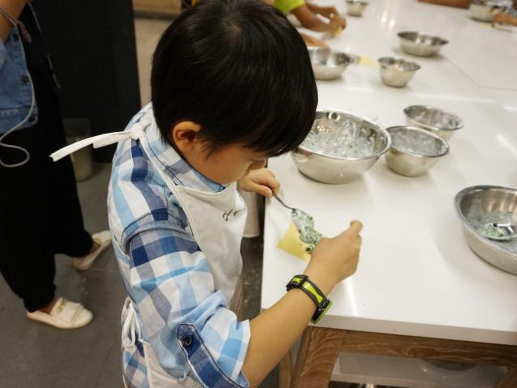 Anak-anak mencampurkan bahan untuk ravioli. Kemudian memasukkanya ke dalam adonan pasta dan melipatnya.