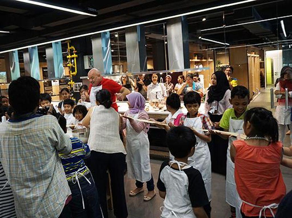 Salah satu kegiatan yang menarik, anak-anak diminta membantu menggiling adonan pasta. Menjadi lembaran yang sangat panjang. Bahkan di sesi kedua, ada 20 anak yang memegang hasil gilingan adonan tersebut.