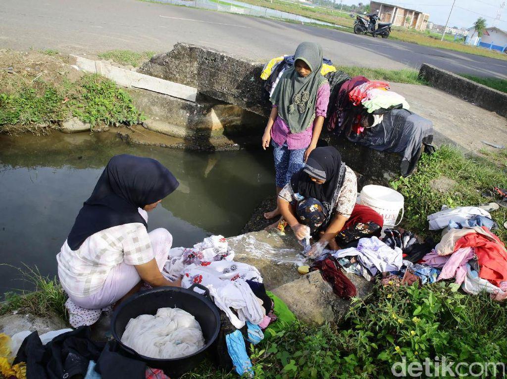 Korban Gempa Aceh Cuci Pakaian di Parit