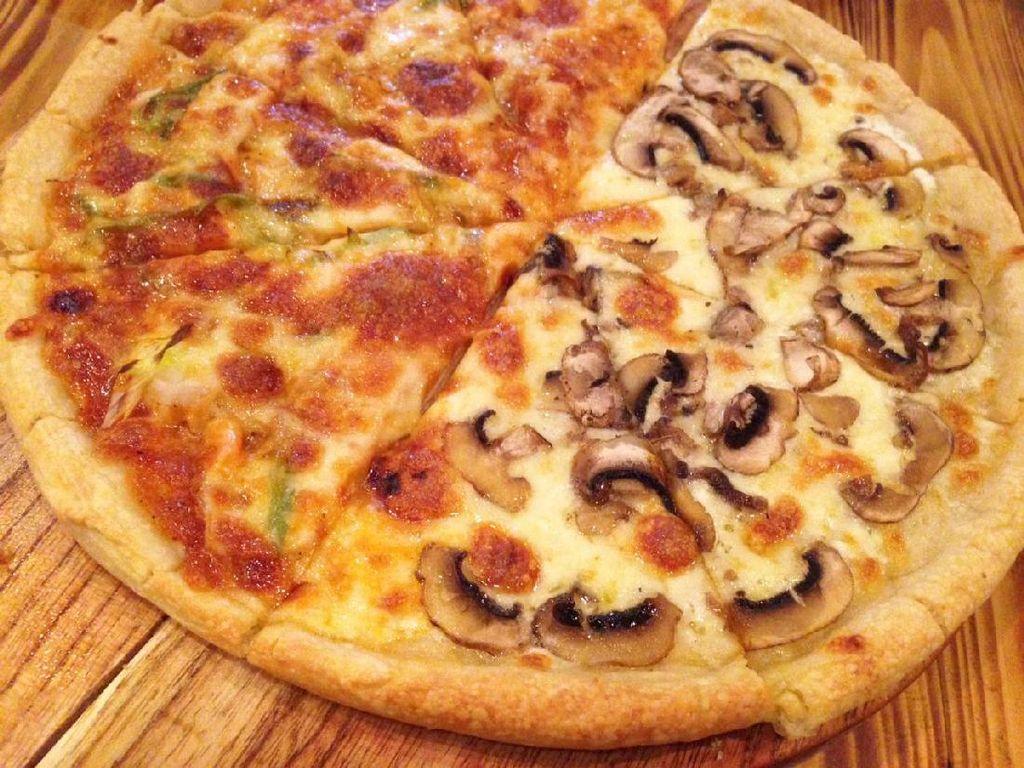 Di sini pizza bisa dipesan dengan dua rasa berbeda dalam satu porsi. Seperti custom pizza dengan rasa BBQ Chicken dan Truffle Mushroom. Topping BBQ Chicken beraroma smoky wangi dan bercitarasa gurih. Sementara pizza truffle mushroom dominan rasa keju dengan jejak aroma minyak truffle.