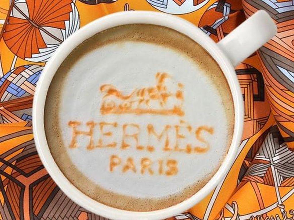 """Tulisan """"Hermes Paris"""" warna oranye ikut mempercantik latte. Latar scarf Hermes menambah semarak foto."""