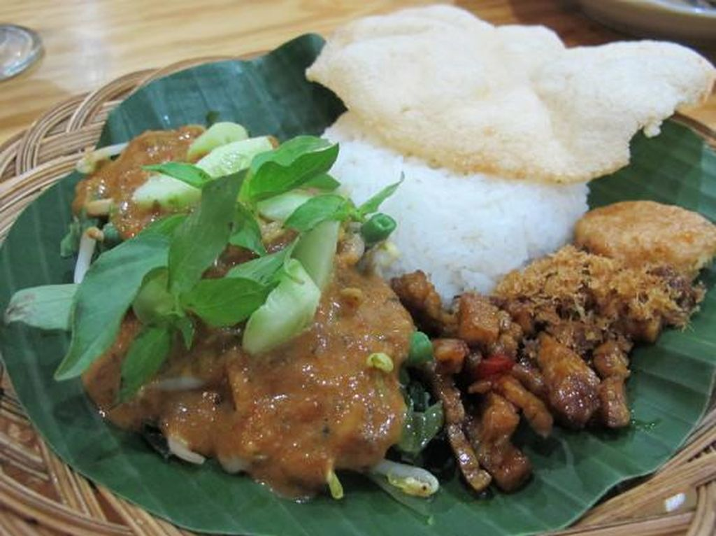 Di warung Pecel Pincuk Godong Ijo ini pecel disajikan dengan cincangan mentimun, daun kemangi dan orek tempe yang manis gurih.Foto: detikFood
