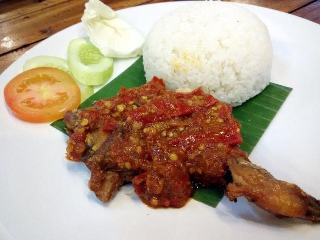 Mampir ke Dapoer Kampoeng di Ciputat? Jangan lupa cicip ayam penyet berbalur sambal merah di sini. Rasa asam segarnya bisa bikin ketagihan!