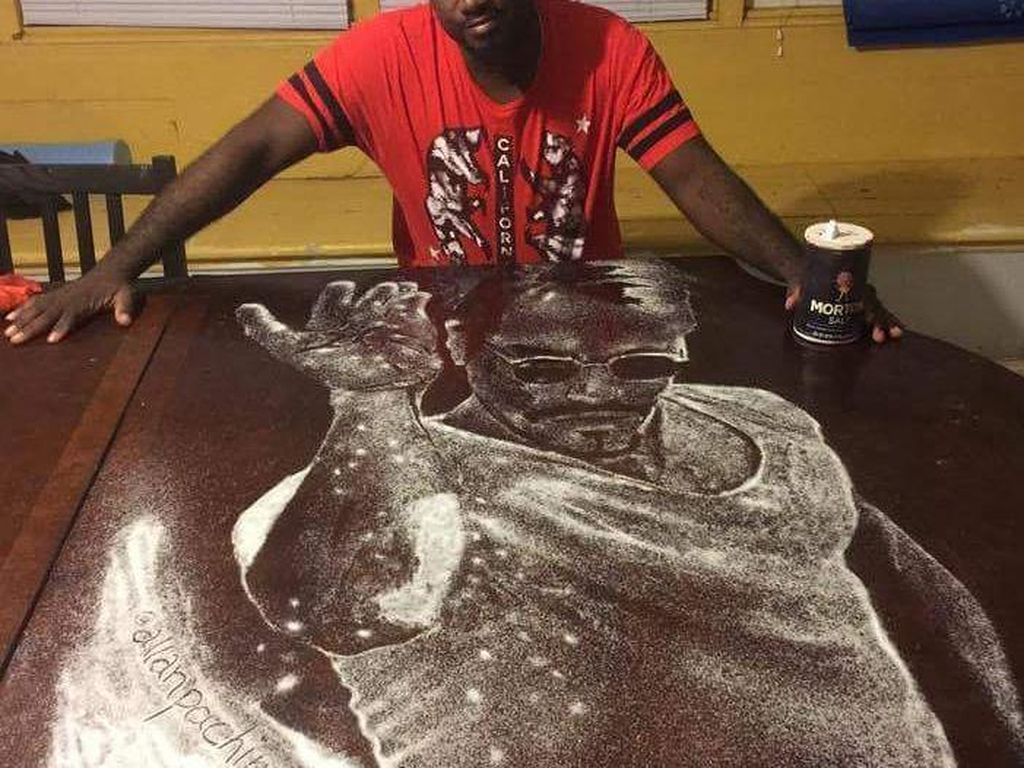 Allan Pachino Wallace membuat lukisan Salt Bae dengan garam. Di atas meja berwarna cokelat tua terlihat pria sedang menaburi garam. Mirip gak? (Foto: Istimewa)