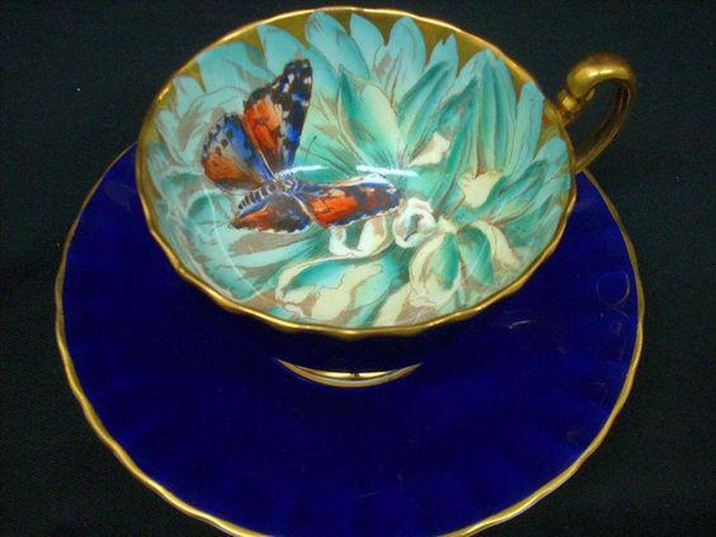 Wah, yang ini lebih cantik! Kupu-kupu ada di dalam cangkir Aynsley dengan warna biru tua di bagian luar dan biru kehijauan di bagian dalam. Sebaiknya gunakan untuk menyeduh teh putih atau teh hijau yang bening agar gambar kupu-kupus bisa terlihat. (Foto: Istimewa)