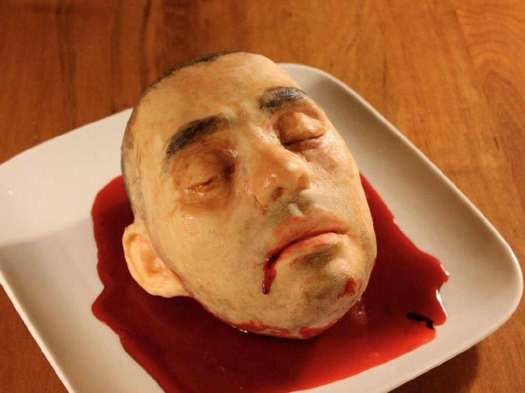 Terinspirasi dari kepala dan wajah sang suami, Katherine membuat cake yang bentuknya benar-benar mirip seperti wajah manusia. Yang lebih menyeramkan lagi ada lumuran darah yang seakan keluar dari kepalanya. Padahal di dalam kepala ini ada red velvet cake yang enak.  Foto: Bussines Insider