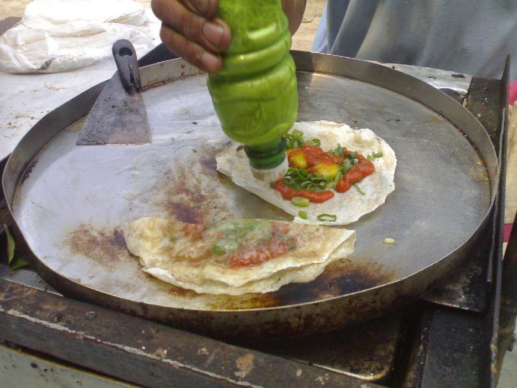 Martabak telur ala jajanan SD ini agaknya berbeda. Loyang datar yang diberi sedikit minyak digunakan untuk memasak kulit lumpia yang didalamnya diberi telur puyuh, irisan daun bawang, bumbu bubuk dan juga saus. Harganya beragam, untuk penggunaan telur puyuh dibandrol dengan harga Rp 3.000 dan telur ayam dibandrol dengan harga Rp 5.000 per porsinya. (Foto: Istimewa)