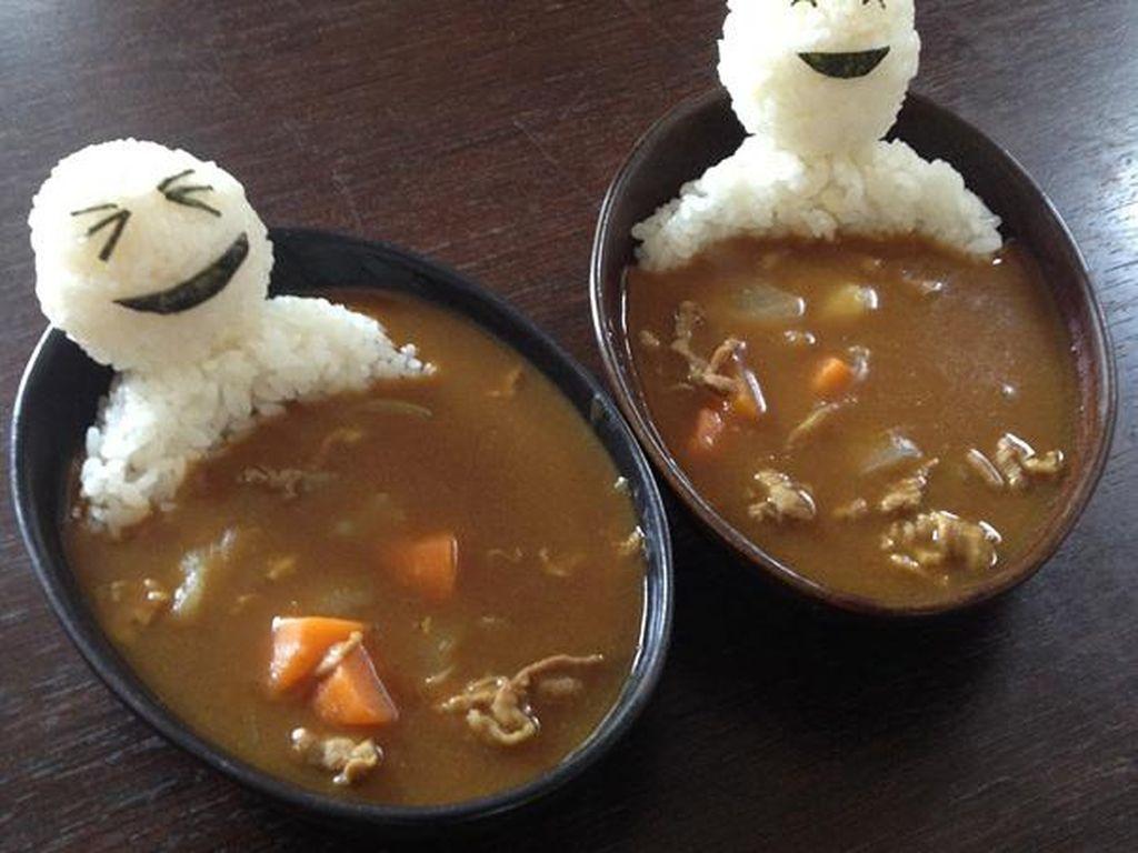 Boneka yang sedang tersenyum ini adalah nasi. Disiram dengan kuah kari yang gurih kental, justru terlihat seperti sedang berendam dalam onsen kari. Foto: Istimewa