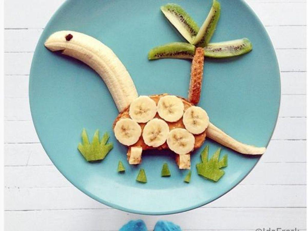 Sekilas bentuknya memang seperti dinosaurus. Terdiri dari roti, selai kacang, potongan buah pisang serta aneka buah-buahan lain seperti kiwi. Dinosaurus ini tampak lucu dengan paduan hiasan rumput dan pohon. Menggemaskan kan? Foto: Istimewa