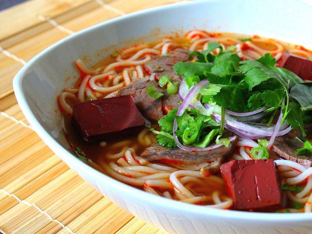 Bun Bo Hue merupakan mie kuah pedas dengan topping daging dari kota Hue, Vietnam. Perlu waktu berjam-jam merebus daging dan menambahkan aneka herba wangi untuk keseimbangan rasa pedasnya. Sajian ini bisa ditambahkan potongan dadu darah babi beku yang warnanya cokelat marun seperti hati sapi dan tekstur mirip tahu. Foto: Istimewa